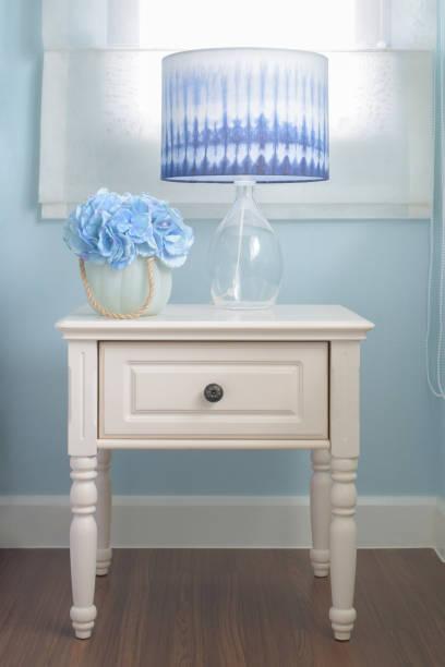 blume glas und lesung lampe auf nachttisch in hell blau innen schlafzimmer - hellblaues zimmer stock-fotos und bilder