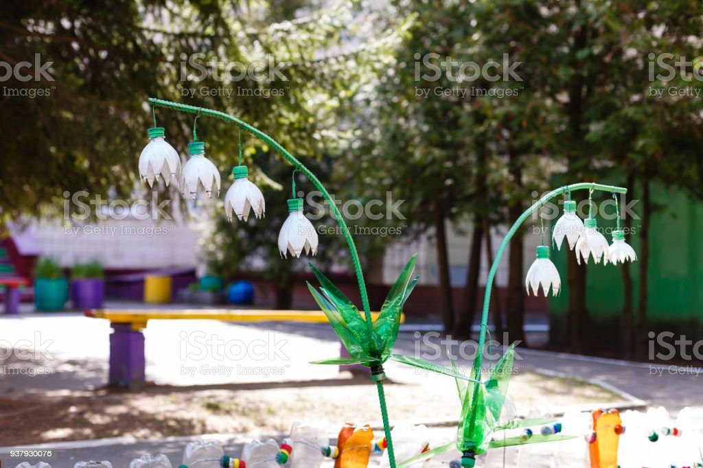 Flower lily of the valley made of white plastic bottles in the garden Decor of plastic bottles stock photo