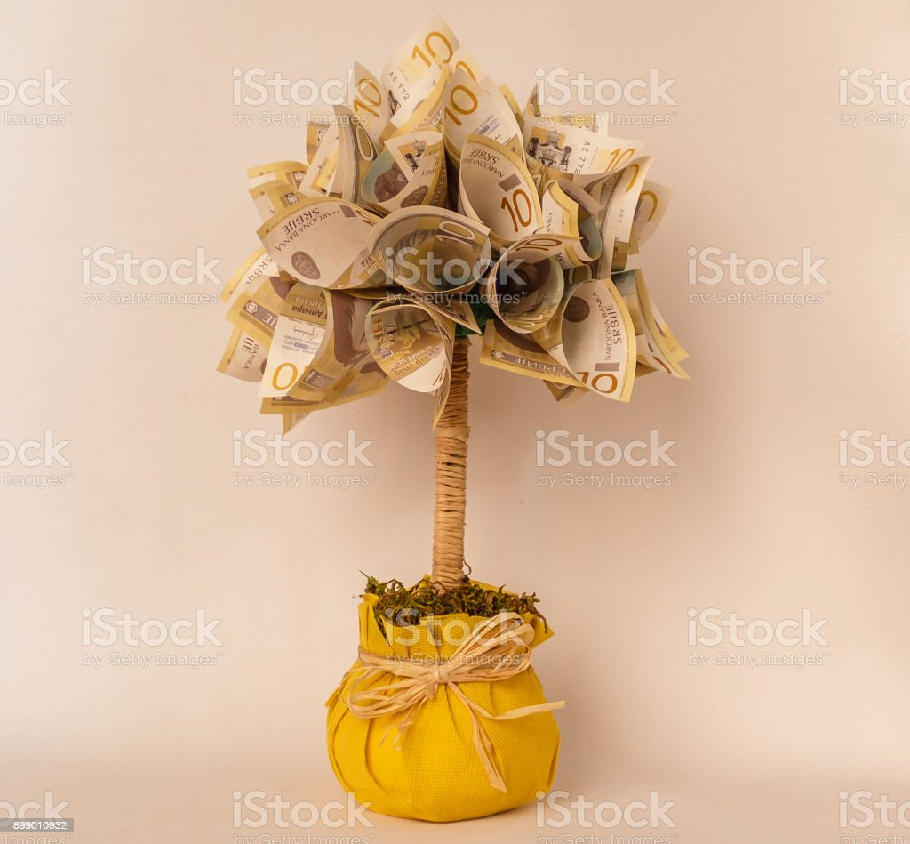 Flower made of a lot of bills in a yellow pot stock photo