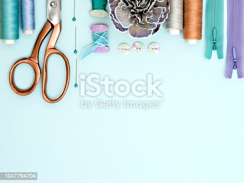 From above shot of cute cloth flower lying near set of assorted sewing tools on light blue background.
