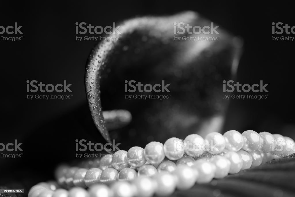 Flower of black calla and white pearl necklace stock photo