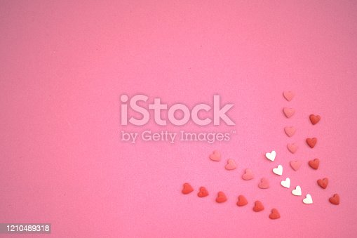 157527860 istock photo Flower of small white, pink and red hearts on a pink paper background 1210489318