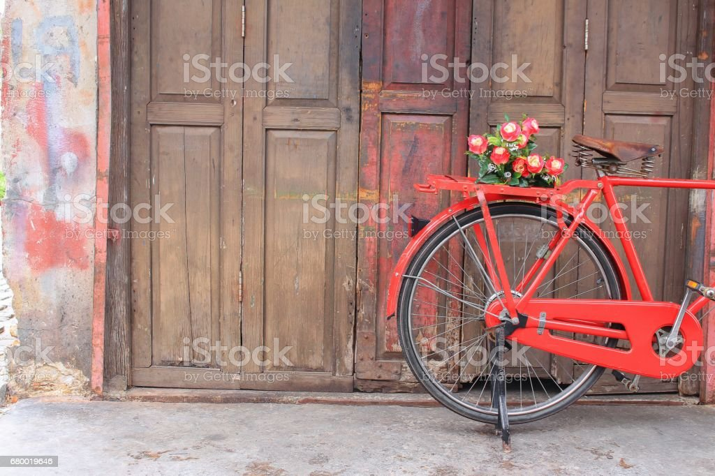 flower on saddle red bicycle classic vintage on wall wood background stock photo
