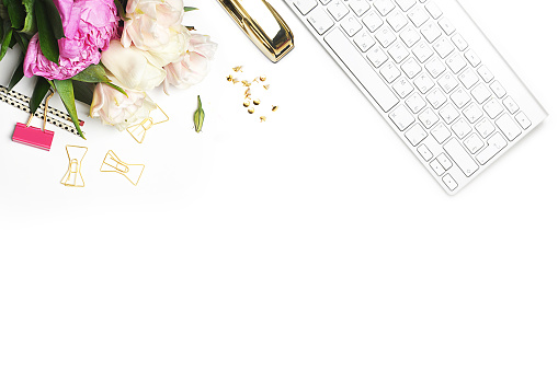 Flower on the table. Keyboard and stapler. Home workplace. Table view. Business accessories. Mock-up background.Peonies