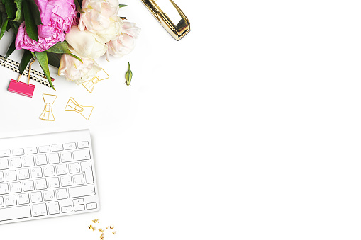 Flower on the table. Keyboard and stapler. Home workplace. Table view. Mock-up background. Peonies