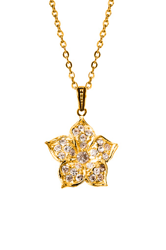 Gold flower pendant with crystals hanging on a chain isolated over white