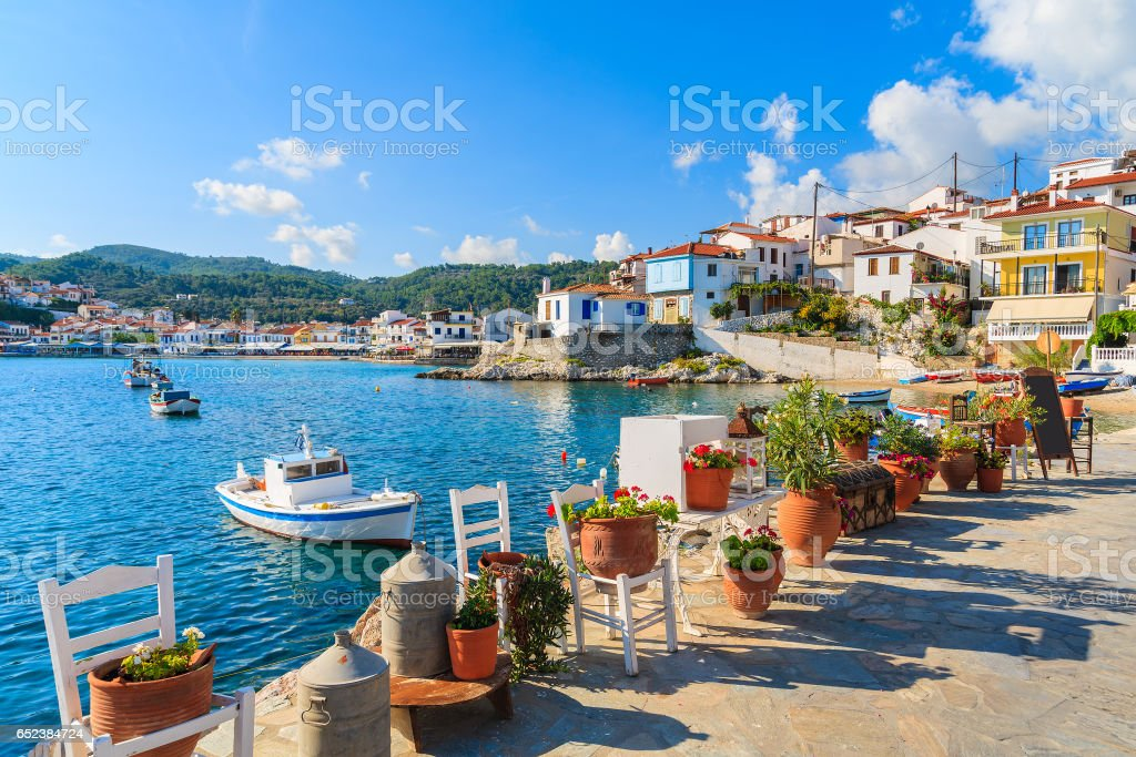 Flower pots on and view of fishing boats anchoring in Kokkari bay, Samos island, Greece stock photo