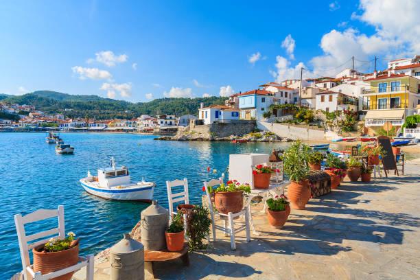 sur les pots de fleurs et l'affichage de pêche bateaux jetant l'ancre dans la baie de kokkari, l'île de samos, grèce - grece photos et images de collection