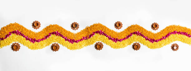 flower rangoli for diwali or pongal made using marigold or zendu flowers and red rose petals over white background with diwali diya in the middle, selective focus - diwali stock pictures, royalty-free photos & images