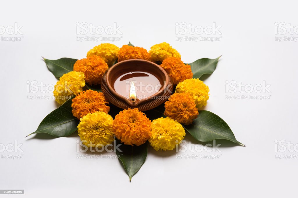 Flower Rangoli For Diwali Or Pongal Or Onam Made Using Marigold Or Zendu Flowers And Red Rose Petals Over White Background With Diwali Diya In The Middle Selective Focus Stock Photo