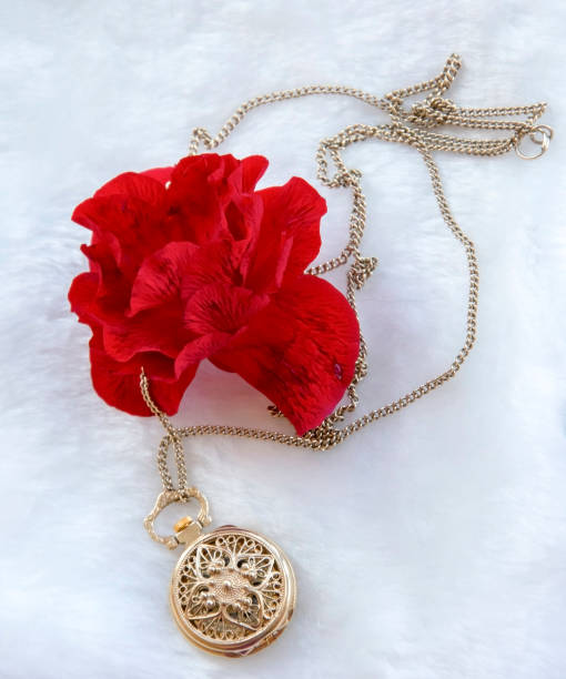 flower red rose and gold filigree work clock - pendant with lid lay on white fur - filigree stock photos and pictures