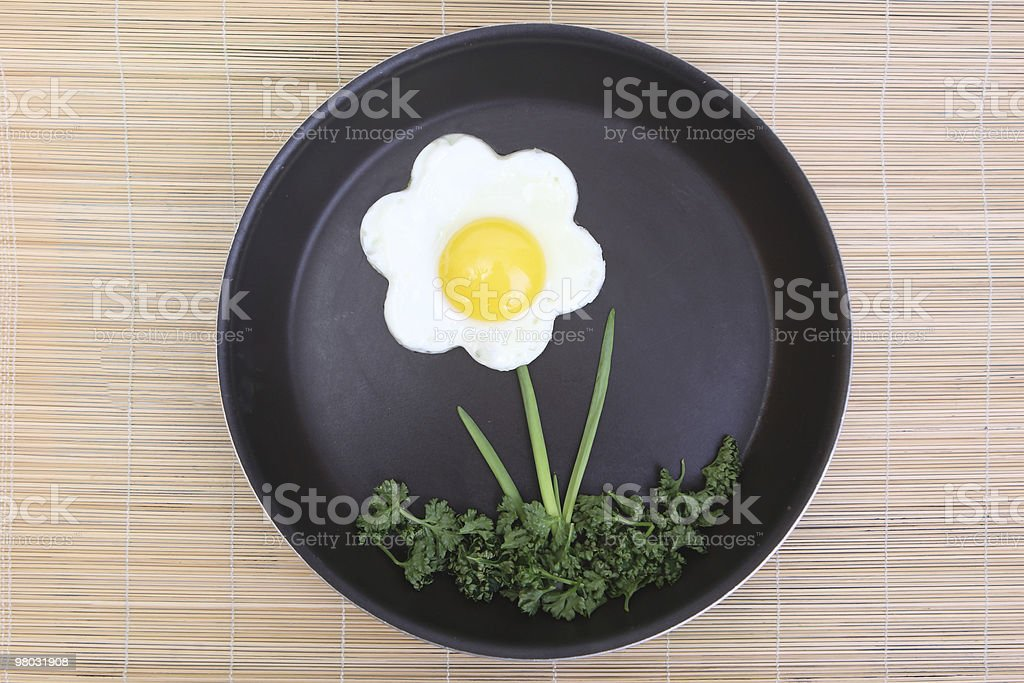 Flower shaped fried egg with greenery royalty-free stock photo