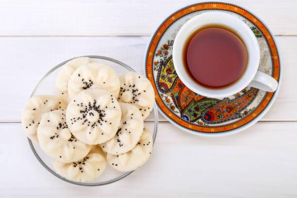 blume geformt persische süß reis kekse (naan berenji) mit mohn-samen und paisley design tasse und untertasse tee auf weißem holz hintergrund draufsicht erschossen - paisley kuchen stock-fotos und bilder