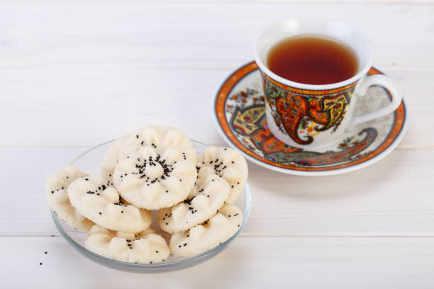 blume geformt persische süß reis kekse (naan berenji) mit mohn-samen und paisley design tasse und untertasse tee auf weißem holz hintergrund - paisley kuchen stock-fotos und bilder