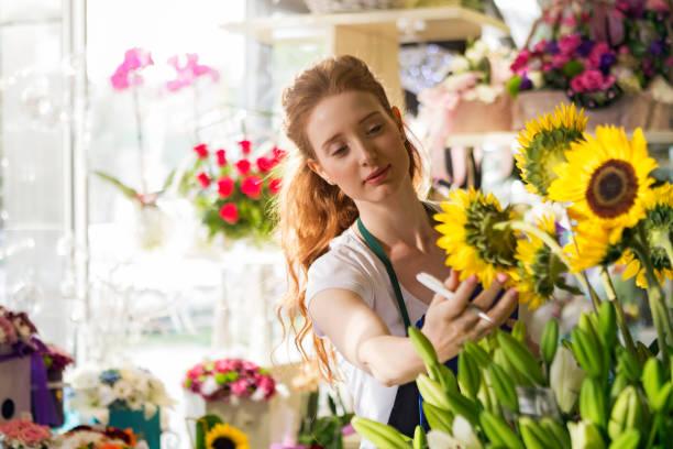 magasin de fleurs, dirigée par la jeune femme - fleuriste photos et images de collection