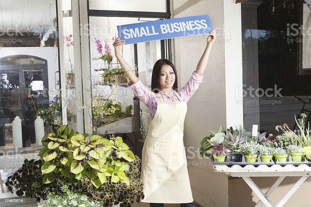 A Happy young woman entrepreneur business owner in front of her...