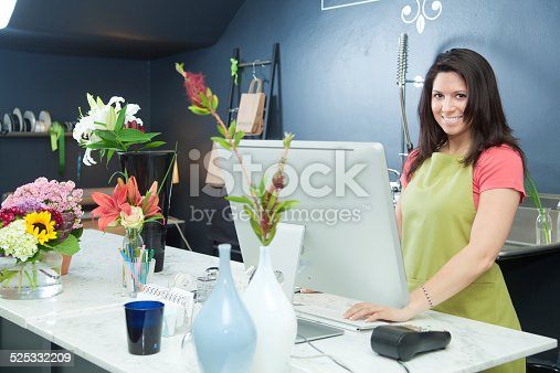 Subject: A small business owner entrepreneur florist working at her flower shop check-out counter.