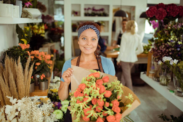 Flower Shop Worker Close up of a flower shop worker holding a flower homegrown produce stock pictures, royalty-free photos & images