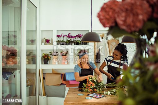 Close up of a flower shop worker teaching the new employee