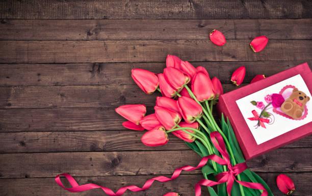 Blume. Tulpe. Frühling Blumen. Bouquet von roten Tulpen mit Geschenk-Box auf dunklem Holz. Gruß für Frauen, Muttertag, Valentinstag. Textfreiraum – Foto