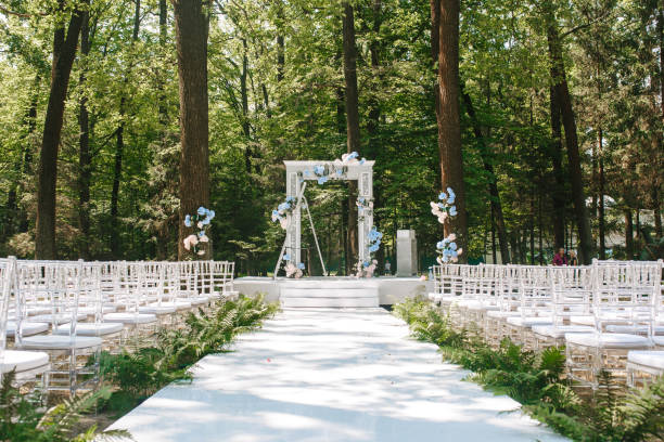 A flower wedding arc stands in the nature in a park on a sunny day. Front view with chairs stock photo