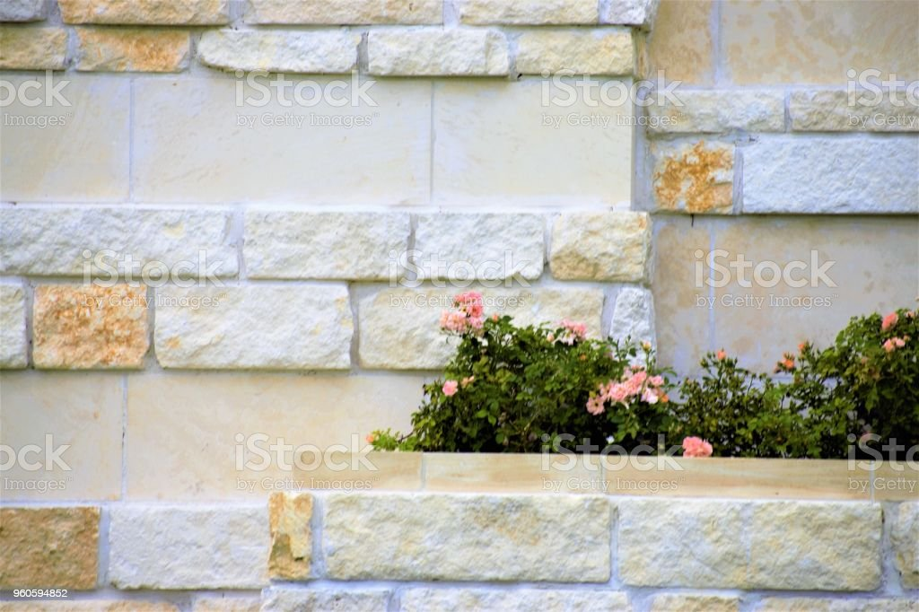 A Flowerbed In The Middle Of A Brick Wall Stock Photo More