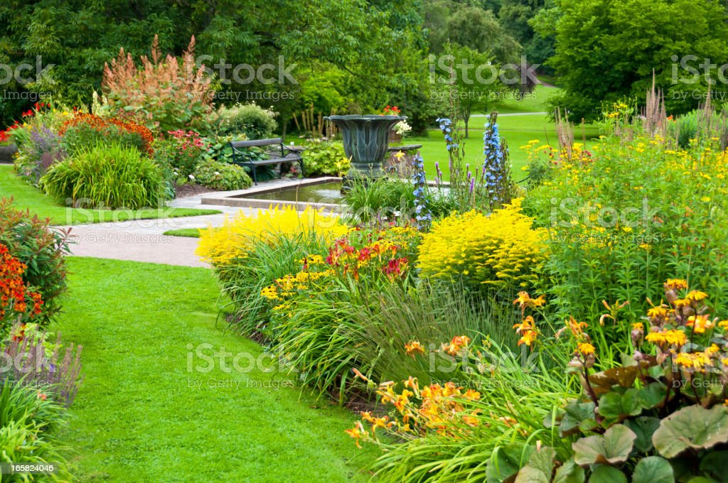 Flowerbeds, lawn and pond in a beautiful park stock photo
