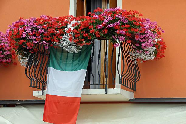 Blühenden Balkon mit Geraniums und die italienische Flagge – Foto