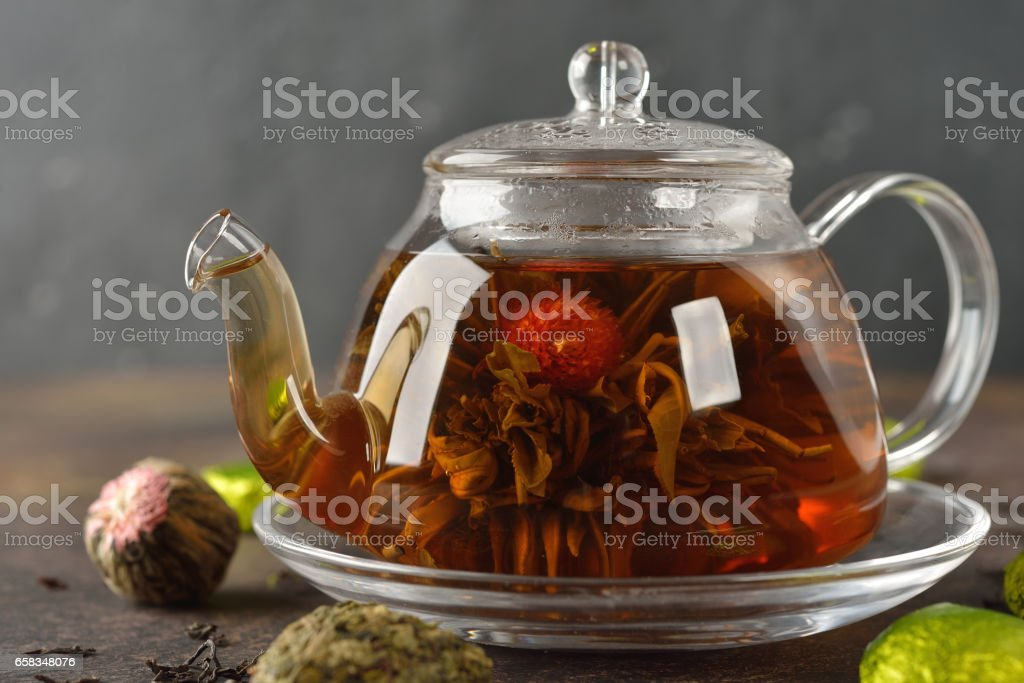 Flowering tea in a glass teapot stock photo