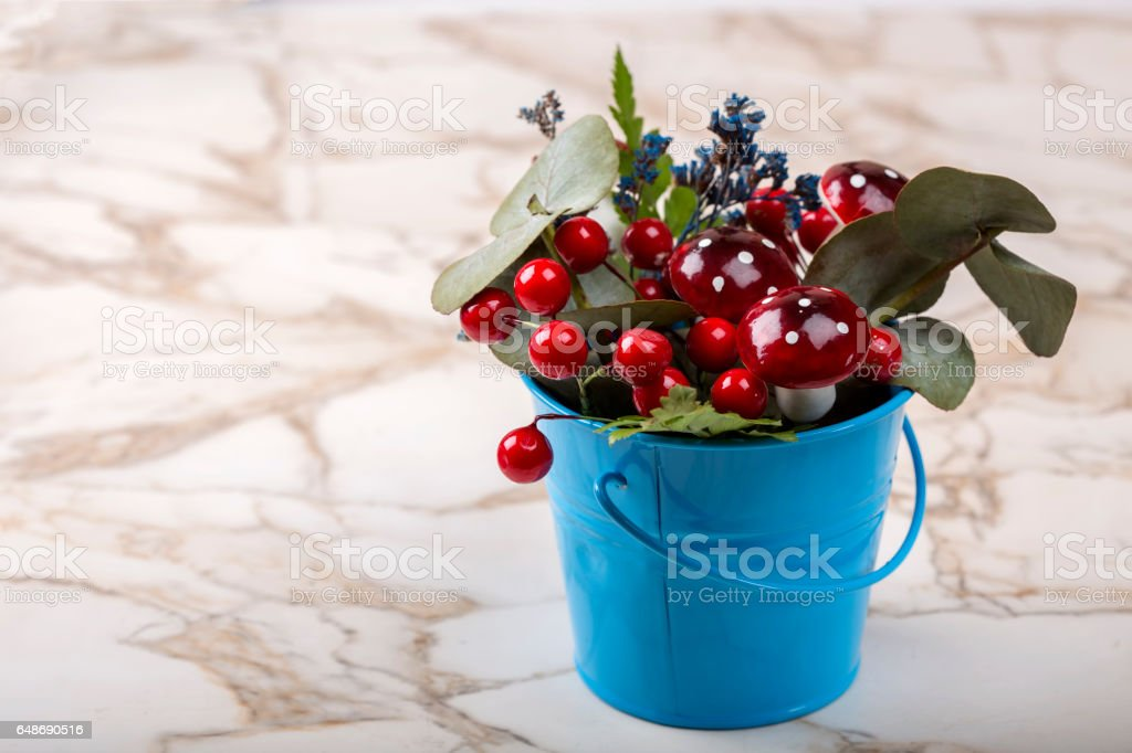 Flowerpot decoration with natural green plant and flowers and artificial mushrooms stock photo