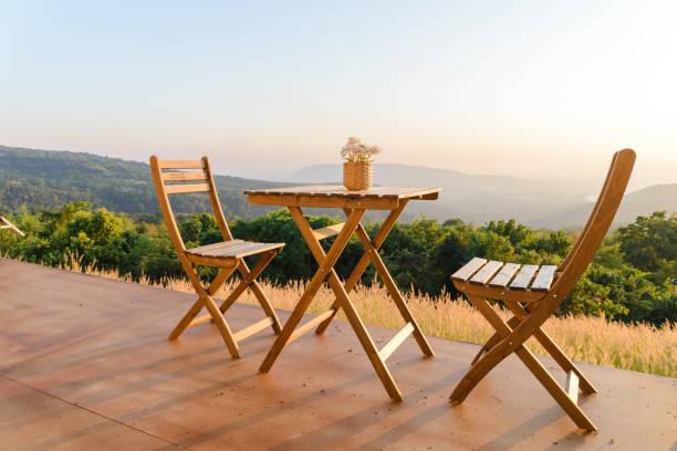 Blumentopf auf Holztisch und Stühle auf der Terrasse. Schöne Sitzgelegenheiten mit Blick auf die Landschaft bei Sonnenuntergang. – Foto