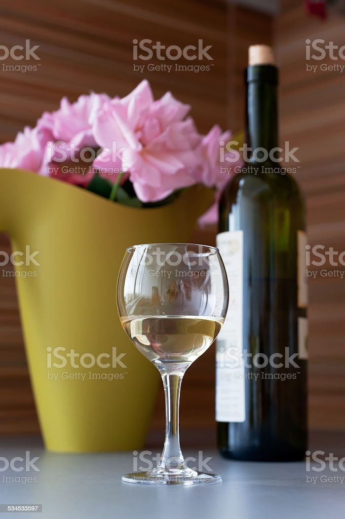 Flowers, a bottle and a glass of wine stock photo