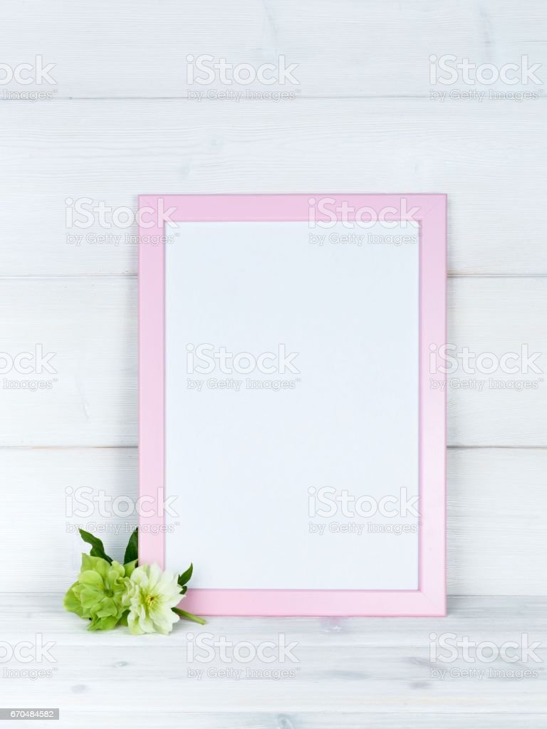 Flowers and a photo frame on a wooden background. stock photo