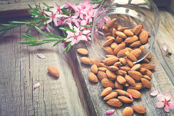 Flowers and almond nuts on a scattering stock photo
