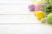 Flowers and easter eggs decoration on rustic wooden background.