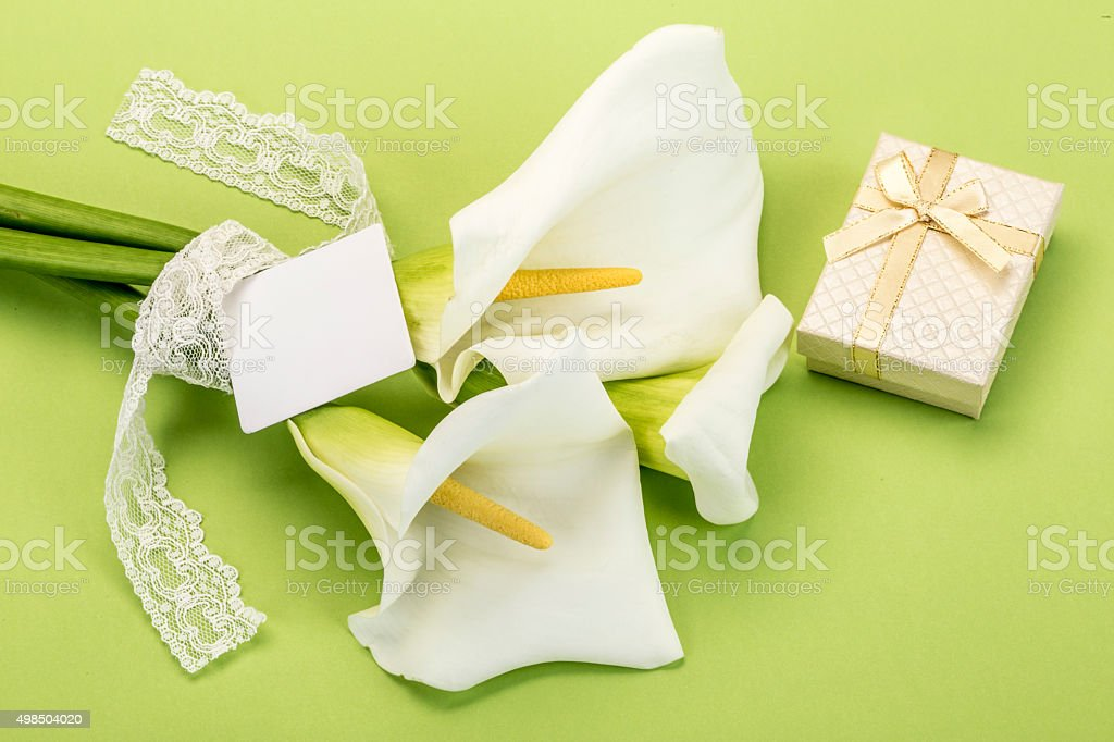 white lilly flowers and a gift box on green
