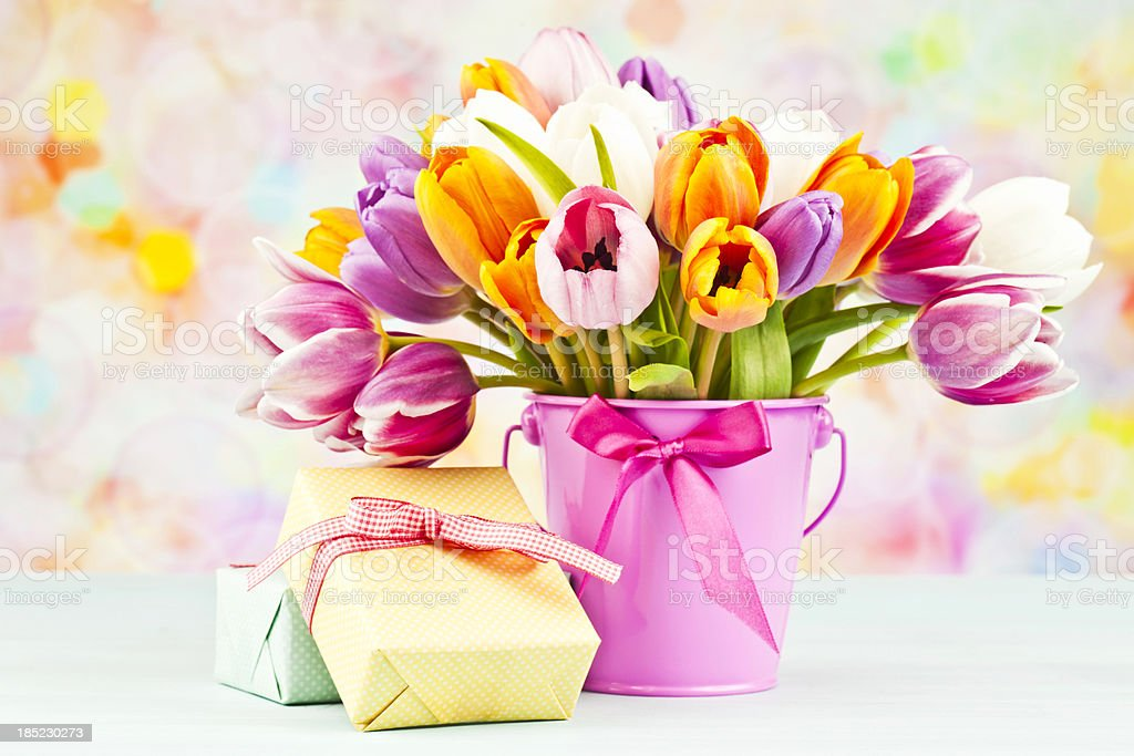 Beautiful bunch of tulips in pink pail with two wrapped gifts.