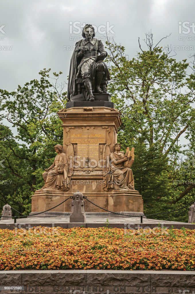 Flowers and monument with the statue of Joost Van Den Vondel in Amsterdam park. stock photo