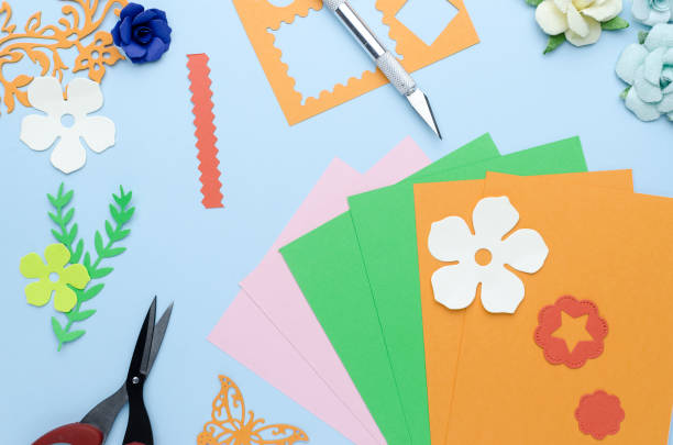 flowers and shapes cut from colored paper scattered on a blue background