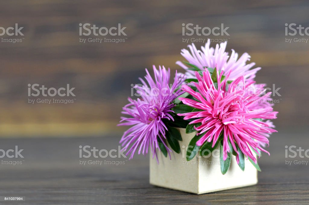 Flowers arranged in gift box on wooden background stock photo