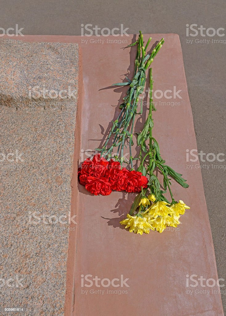 Flowers at war monument stock photo