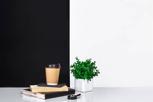 blumen, buch, notizbuch und tasse kaffee, schwarzen und weißen wand - kleiner couchtisch stock-fotos und bilder