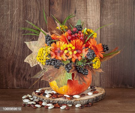 Autumn bouquet in a vase made out of pumpkin for Thanksgiving Day.