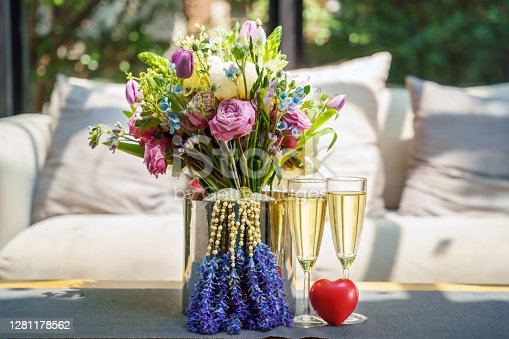 flowers bouquet with two glass of champagne and heart model, concept of valentines day or wedding anniversary celebration