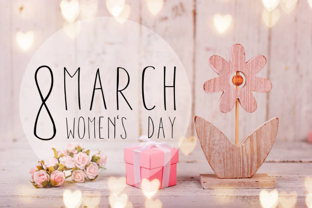 Flowers composition for Women's Day. Pink flowers on old white wooden background stock photo