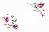 istock Flowers composition. Frame made of eucalyptus branches and rose flowers on white background. Flat lay, top view, copy space 1136118440