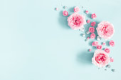 istock Flowers composition. Frame made of rose flowers on pastel blue background. Valentines day, mothers day, womens day, spring concept. Flat lay, top view, copy space 1127776431