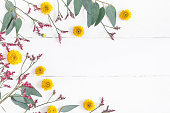 Flowers composition. Frame made of pink, yellow flowers and eucalyptus branches on white wooden background. Flat lay, top view, copy space