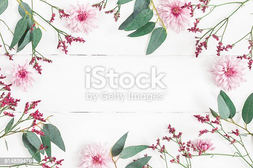 Flowers composition. Frame made of pink flowers and eucalyptus branches on white wooden background. Flat lay, top view, copy space