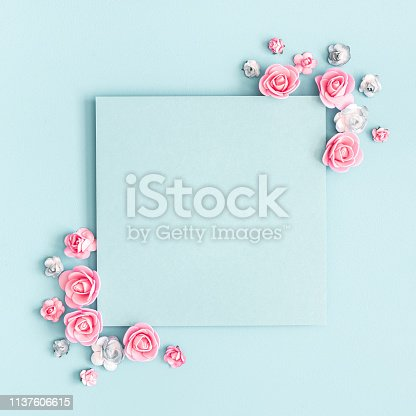 Flowers composition. Paper blank, pink flowers on pastel blue background. Flat lay, top view, copy space, square